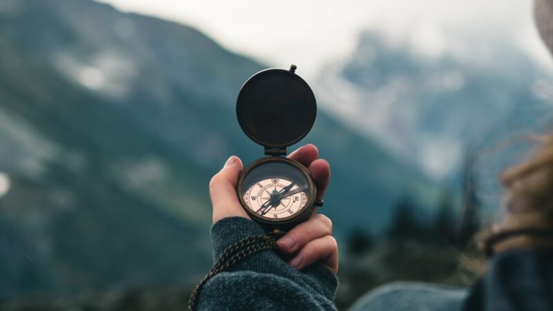 Employee experience blog - woman holding compass and looking at mountains