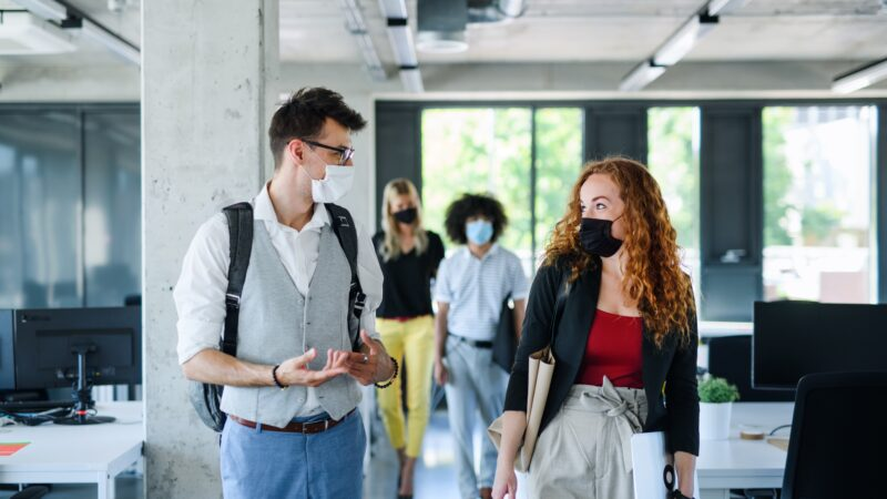 work-from-home post-pandemic work - group of colleagues walking in an office with masks on